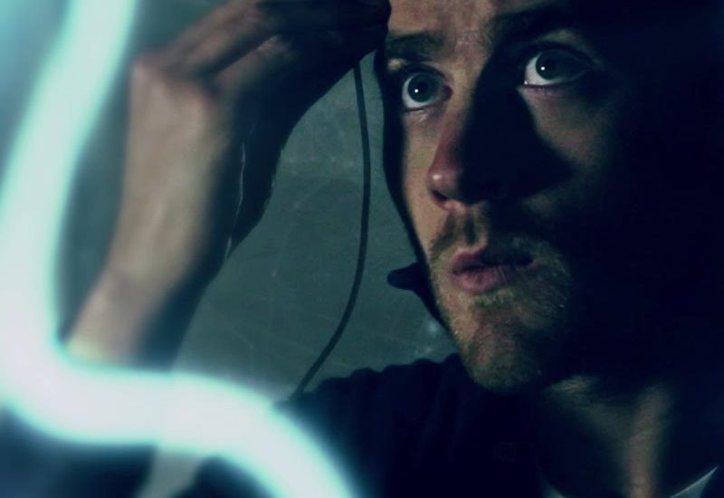 Still from sci-fi music video Falling in Love — Hero attaches a node to his forehead