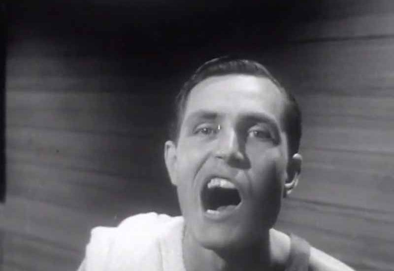 Still from The Fanfare music video for artist Tom Hickox — archive footage from a 1940s PSA where a man checks his teeth in a mirror