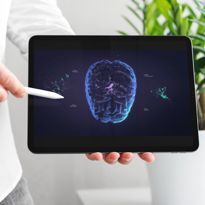 A person in a white coat points to an ipad showing a 3D visualization of a human brain