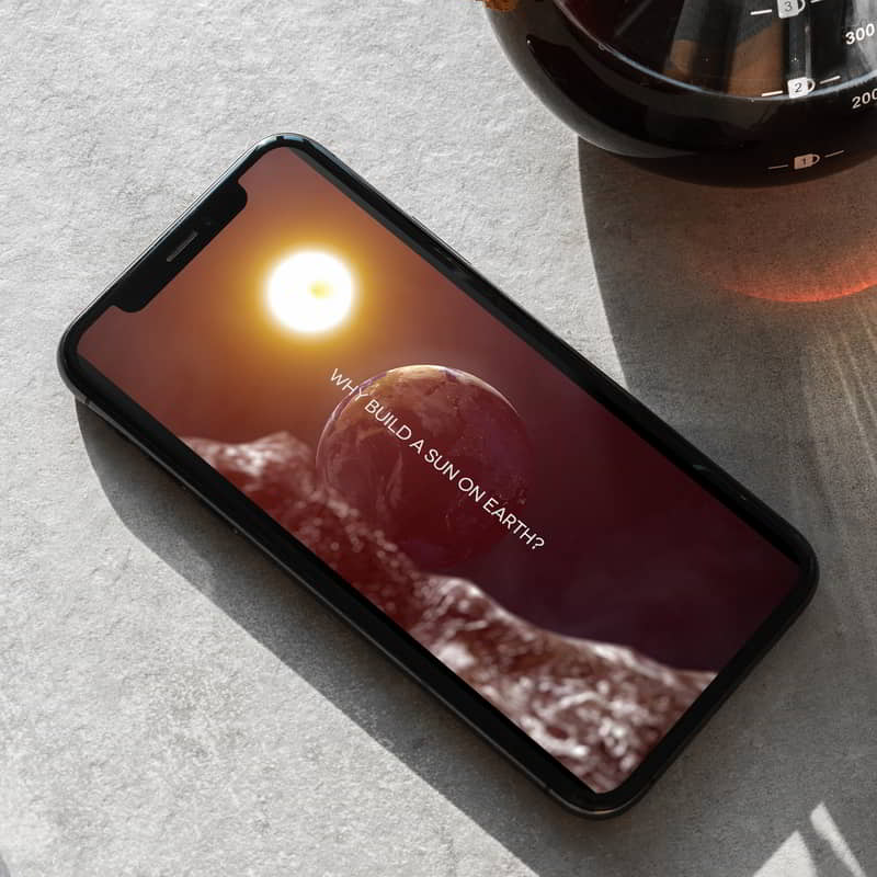 Phone beside a coffee jar. The phone shows a still from the film 'Why Build a Sun on Earth?'. It shows Earthrise from the moon.